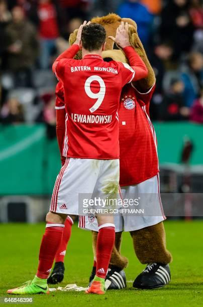 Bayern Munich's Polnish striker Robert Lewandowski makes high five with mascot Berni after the German Cup DFB Pokal quarterfinal football match FC...