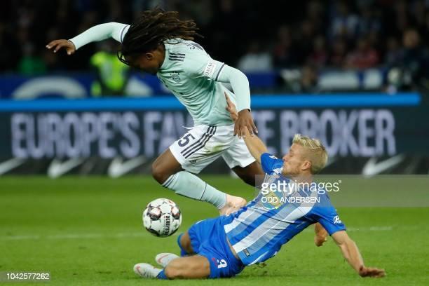 Bayern Munich's Portuguese midfielder Renato Sanches is challanged by Berlin's Norwegian midfielder Per Ciljan Skjelbred during the German first...