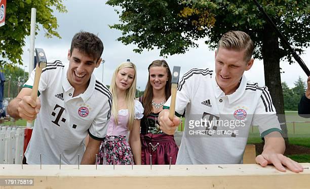 Bayern Munich's Spain midfielder Javi Martinez and Bayern Munich's midfielder Bastian Schweinsteiger play a traditional funfair game during the...