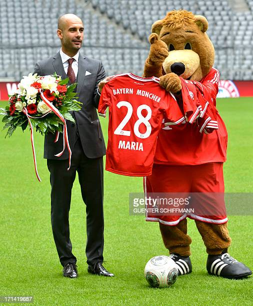 Bayern Munich's Spanish head coach Pep Guardiola gets a trikot for his daughter Maria from maskot Berni after the press conference with the new...