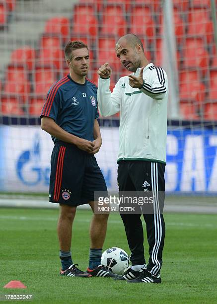 Bayern Munich's Spanish head coach Pep Guardiola speaks with Bayern Munich's defender Philipp Lahm during a training session on the eve of the UEFA...