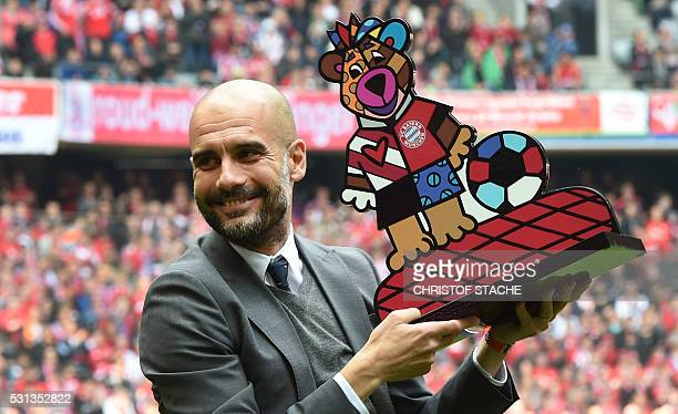 Bayern Munich's Spanish headcoach Pep Guardiola holds a gift prior the German first division Bundesliga football match between FC Bayern Munich and...