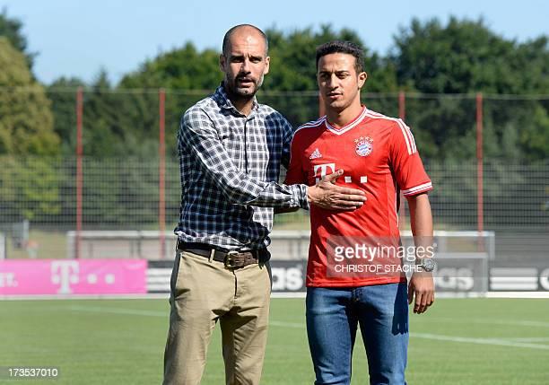Bayern Munich's Spanish headcoach Pep Guardiola presents Bayern Munich's new Spanish midfielder Thiago Alcantara at their training grounds in Munich,...