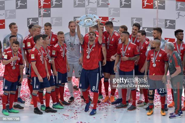 Bayern Munich's Spanish midfielder Javier Martinez lifts the trophy at the end of the German first division Bundesliga football match FC Bayern...