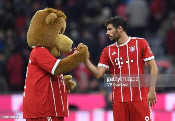 Bayern Munich's Spanish midfielder Javier Martinez shakes hands with his club's mascot Berni after the German first division Bundesliga football...