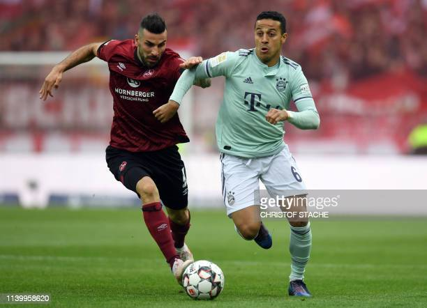 Bayern Munich's Spanish midfielder Thiago Alcantara and Nuremberg's Swedish striker Mikael Ishak vie for the ball during the German first division...