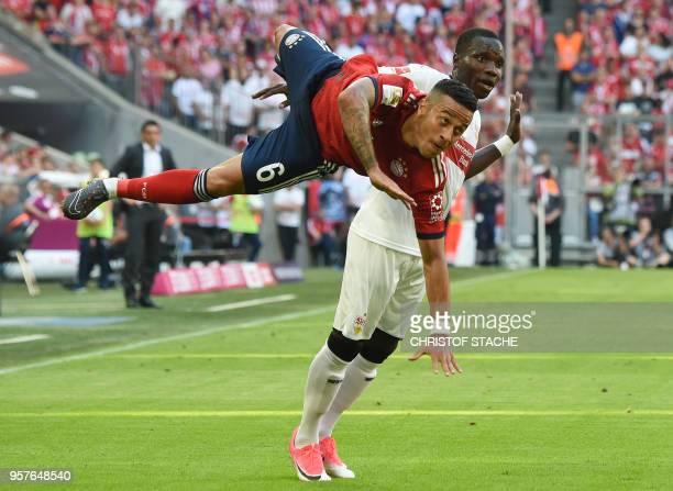 Bayern Munich's Spanish midfielder Thiago Alcantara falls against Stuttgart's Belgian midfielder Orel Mangala during the German first division...
