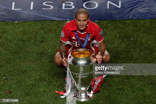 Bayern Munich's Spanish midfielder Thiago Alcantara poses with the trophy after Bayern won the UEFA Champions League final football match between...