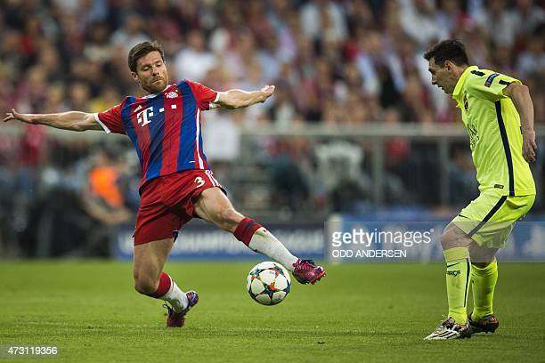 Bayern Munich's Spanish midfielder Xabi Alonso and Barcelona's Argentinian forward Lionel Messi vie for the ball during the UEFA Champions League...