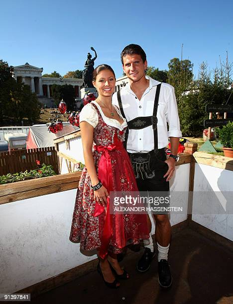 Bayern Munich's striker Mario Gomez and his girlfriend Silvia Meichel dressed in traditional Bavarian clothes pose in a beer tent at the Oktoberfest...