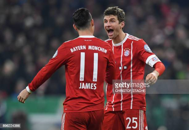 Bayern Munich's striker Thomas Mueller is congratulated by his teammate Colombian James Rodriguez after scoring the second goal during the German...