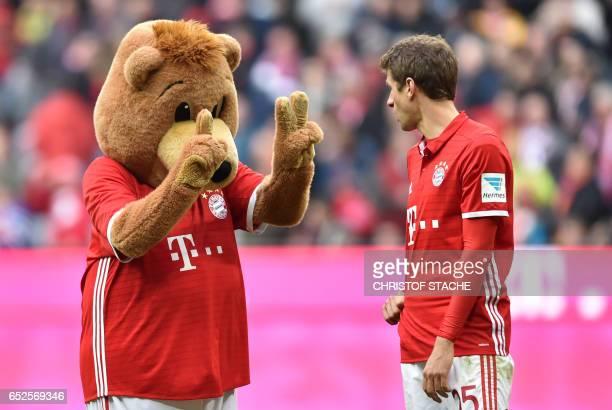 Bayern Munich's striker Thomas Mueller speaks with the Bayern Munich mascot after the German First division Bundesliga football match Bayern Munich...