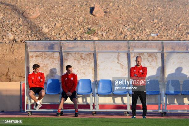 Bayern Munich's Thomas Mueller Philipp Lahm and head coach Pep Guardiola wait for the beginning of the training session after a press conference in...