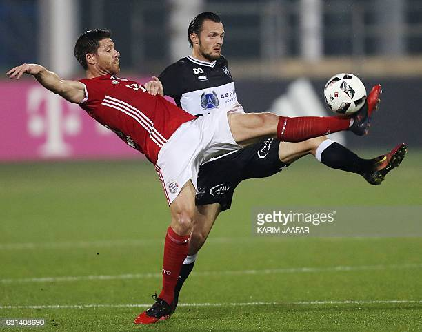 Bayern Munich's Xabi Alonso vies for the ball with Guy Dufour of Belgium's KAS Eupen during a friendly football match at the Aspire Academy in Doha...