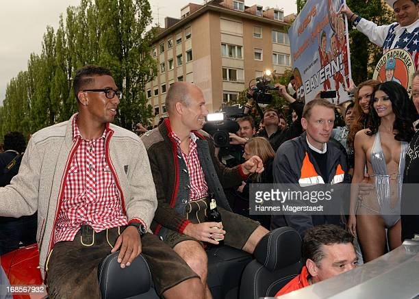 Bayern players Jerome Boateng and Arjen Robben passes Micaela Schaefer while sitting in a car on their way to the Marienplatz square to celebrate the...