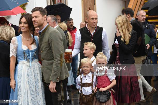 FC Bayern players Xabi Alonso and his wife Nagore Arjen Robben his wife Bernadien and their children can be seen in front of the Kaefer tent at the...