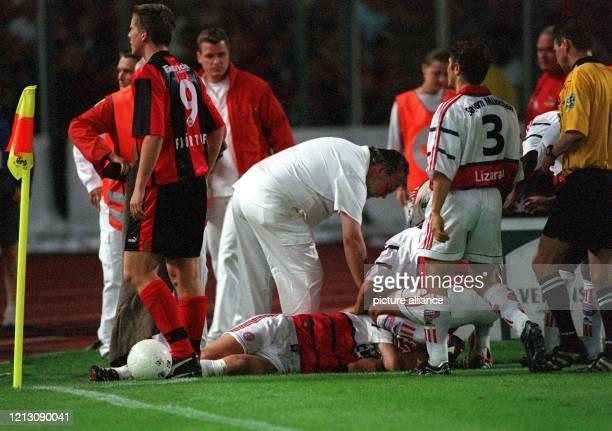 Bayern-Kapitän Stefan Effenberg liegt von Betreuern umringt auf dem Rasen, nachdem er von einer Metall-Pfeife am Kopf getroffen und verletzt wurde....