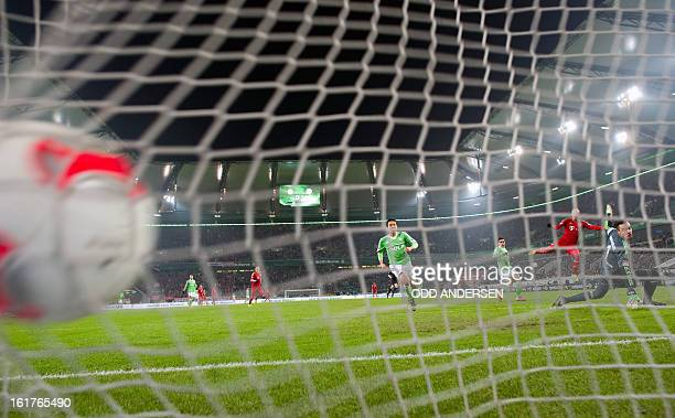 Bayern's Arjen Robben of the Netherlands scores past Wolfsburg keeper Diego Benaglio during the German first division Bundesliga football match VfL...