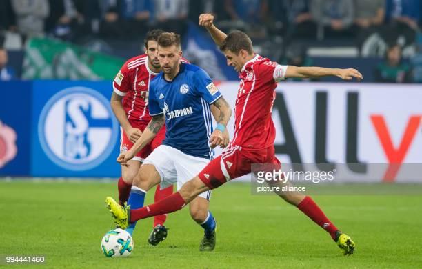 Bayern's James Rodriguez and Bayern's Thomas Mueller in action against Schalke's Guido Burgstaller during the German Bundesliga soccer match between...