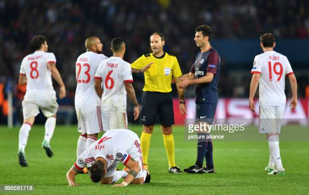 Bayern's Niklas Suele lies on the ground while his team members discuss with referee Antonio Mateu Lahoz during the Champions League football match...