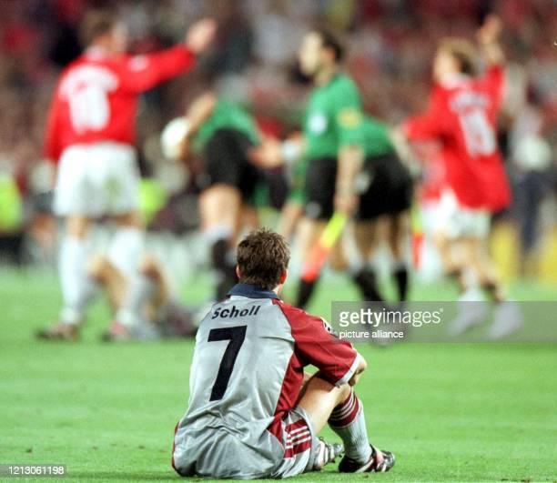 FC BayernSpieler Mehmet Scholl schaut am einsam am Boden sitzend den am anderen Spielfeldende jubelnden Spielern von Manchester United zu Der FC...