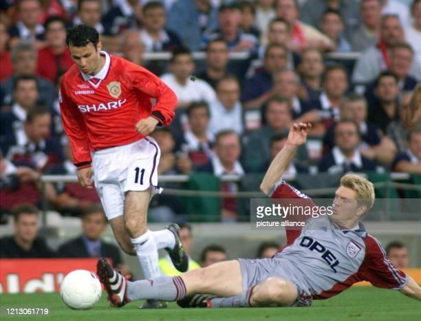 BayernSpieler Stefan Effenberg behindert mit einem langen Bein den ManchesterSpieler Ryan Giggs und sieht für diese Aktion vom Schiri anschließende...