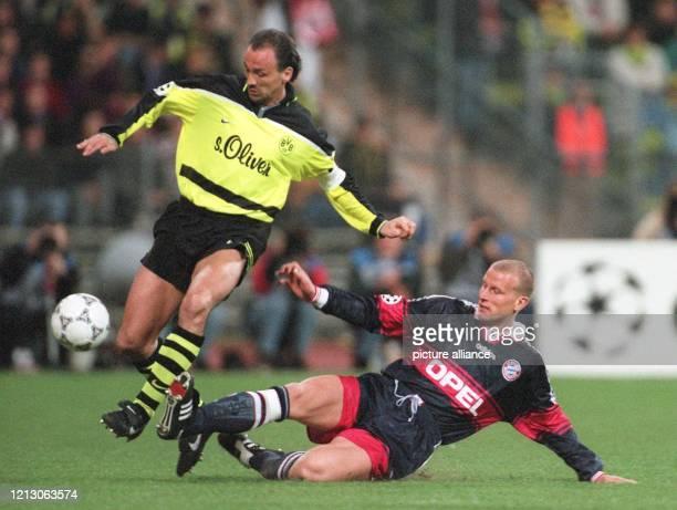 BayernStürmer Carsten Jancker rutscht mit gestrecktem Bein in den Lauf des ballführenden Dortmunder Abwehrspielers Jürgen Kohler Die...