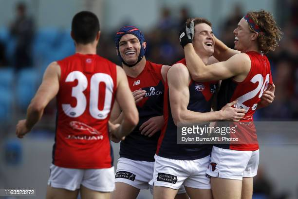 Bayley Fritsch of the Demons celebrates a goal with teammates Jayden Hunt and Angus Brayshaw during the 2019 AFL round 23 match between the North...