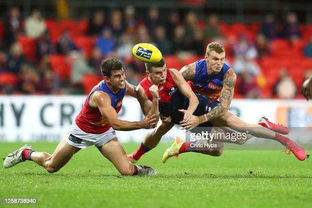 Bayley Fritsch of the Demons handballs whilst being tackled during the round 8 AFL match between the Melbourne Demons and the Brisbane Lions at...