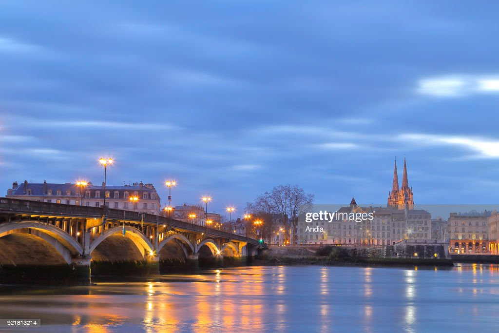 Bayonne at nightfall. The Adour river and the bridge 'pont Saint-Esprit'. In the background, the spires of Bayonne Cathedral (Cathedrale Sainte-Marie de Bayonne).