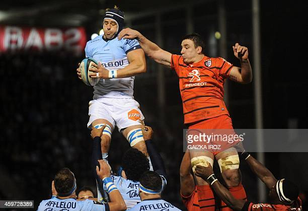 Bayonne's captain Mark David Chisholm grabs the ball in a line out next to Toulouse's number eight Louis Picamoles during the French Top rugby union...