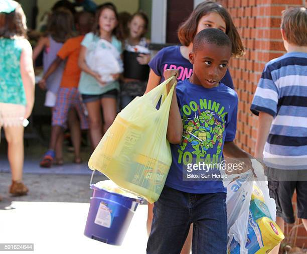Bayou View Elementary School second graders load cleaning supplies at the Gulfport, Miss., school for flood victims in Louisiana on Tuesday, Aug....