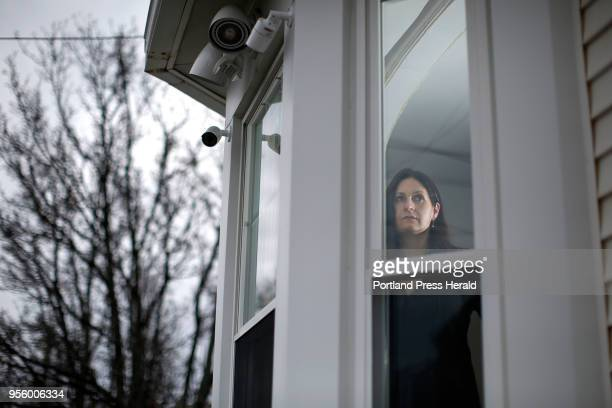 Bayside resident Sarah Michniewicz peers through a window in her Cedar Street home for a portrait. Michniewicz, whose property of 20 years has been...