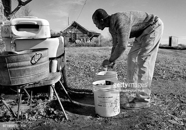Bayview resident Bobby Collins does laundry by hand outside of his shack in Bayview He probably will be able to get out of this shack and move into a...