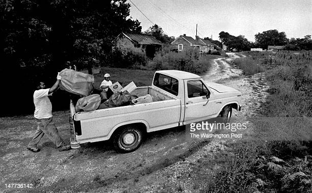 FILE Bayview resident Lawrence Collins Jr and volunteer Rev Anthony Ruffin load up Ruffin's truck as part of a cleanup campaign that Ruffin started...