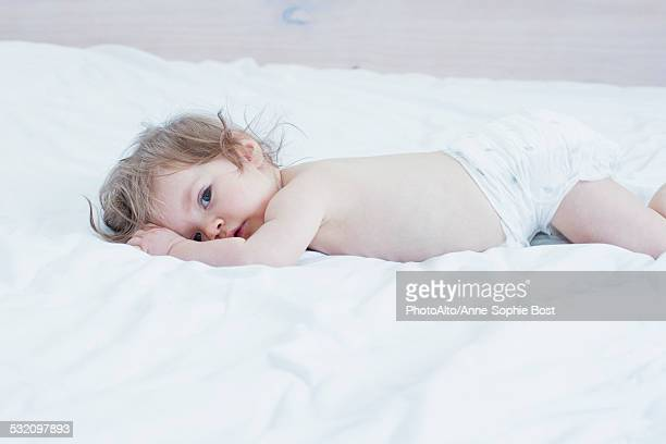 Bbay girl lying on stomach on bed