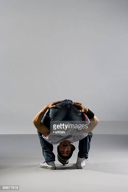 a b-boy doing a freeze  breakdance move - man bending over from behind stock photos and pictures