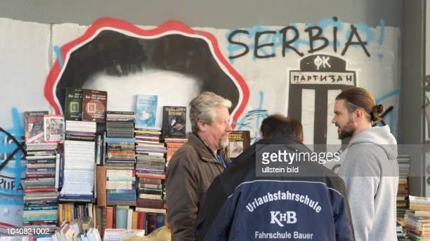 """Bücherflohmarkt vor Wandparole """"Serbien"""" und Logo des Fussballvereins Partisan"""" in Belgrad"""