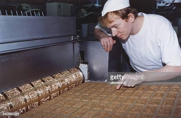 Der Bäcker Josef Kohne gekleidet mit weißer Schutzhaube und TShirt zeigt auf mehrere Spekulatius die auf einem Brett liegen und von einer...