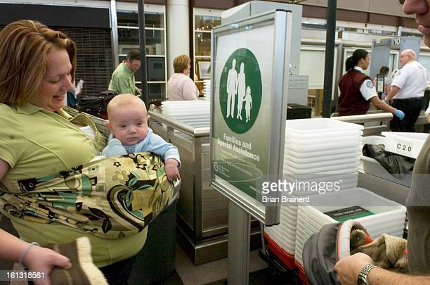 Bcnd20dia_bb_5 -- Jenn Rasmussen of Denver carries baby Blake, age 4 mos, through the green security lane at Denver International Airport Wednesday....