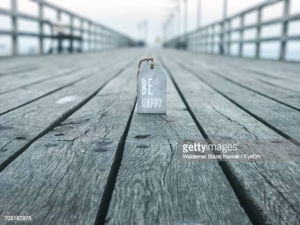 Be Happy Text On Tag At Wooden Pier