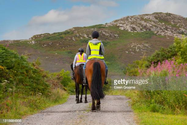 be safe be seen-young couple ride their horses along a country lane in rural wales, wearing hi viz safety wear to be visible to other road users. - horse stock pictures, royalty-free photos & images