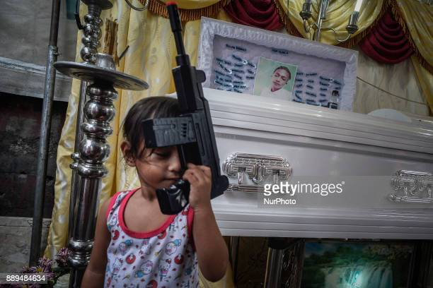 Bea sister of 17yearold Harold Bulan who was killed by unidentified assailants holds a toy gun next to his coffin during his funeral wake in Quezon...