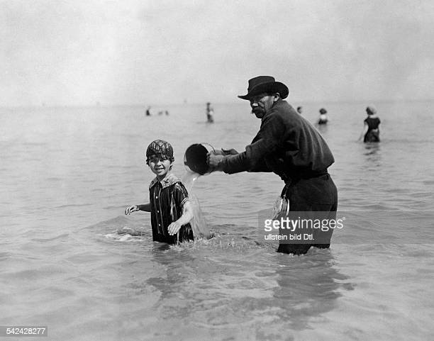 Beach and bathing scenes A man is pouring water with a bucket on a child in the sea at Ostende 1912 Vintage property of ullstein bild