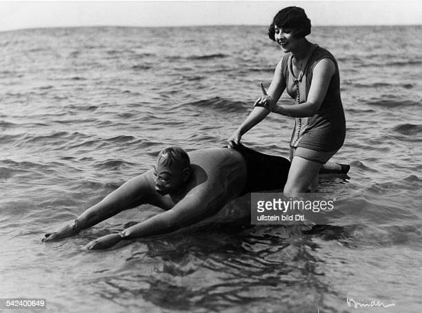 Beach and bathing scenes Hoax in the sea young woman with a male rubber puppet 1929 Photographer Atelier Binder Published by 'Das Neueste von der...