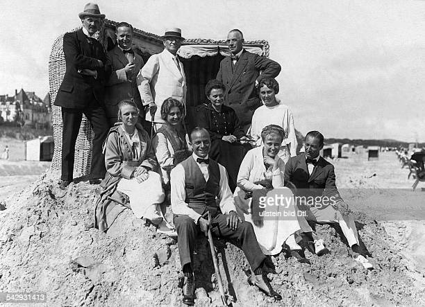Beach and bathing scenes Sitting on a sand hill on the beach; center : Hedwig Courths-Mahler, front left is actor Paul Heidemann and actress Käthe...