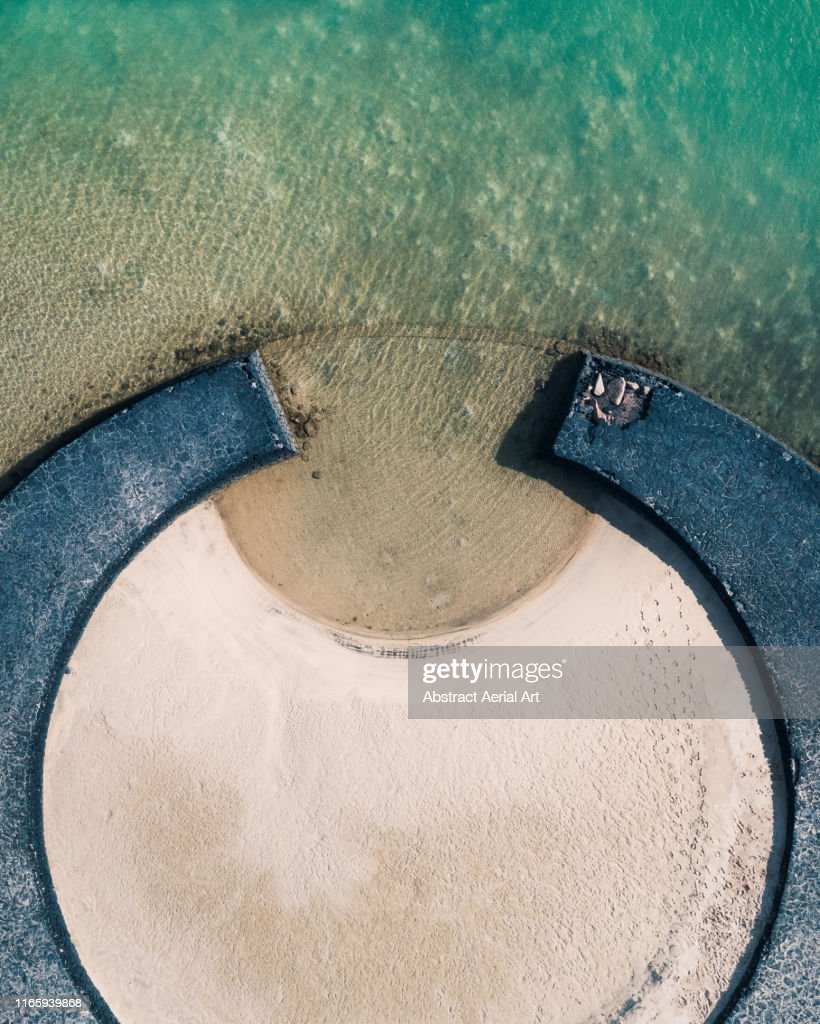 Beach and crescent shaped pier, Lanzarote : Stock Photo