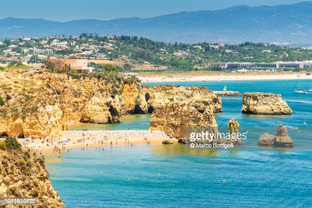 beach and limestone cliffs in summer, algarve, portugal - faro stock photos and pictures