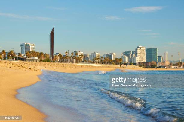 a beach at sunrise in barcelona, spain - barcelona stock pictures, royalty-free photos & images