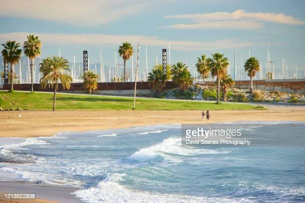 a beach at sunrise in barcelona, spain - la barceloneta stock-fotos und bilder